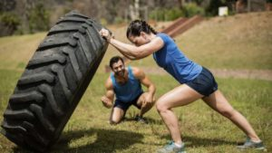 Frau drückt LKW reifen und wird vom Trainer motiviert