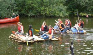 2 Gruppen Floßbauer, paddeln um die Wette auf dem Wasser